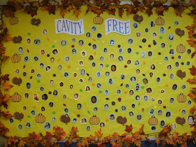 Pictures of children who are cavity-free on a board in the office.