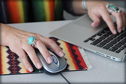 Woman typing on a laptop and holding a computer mouse