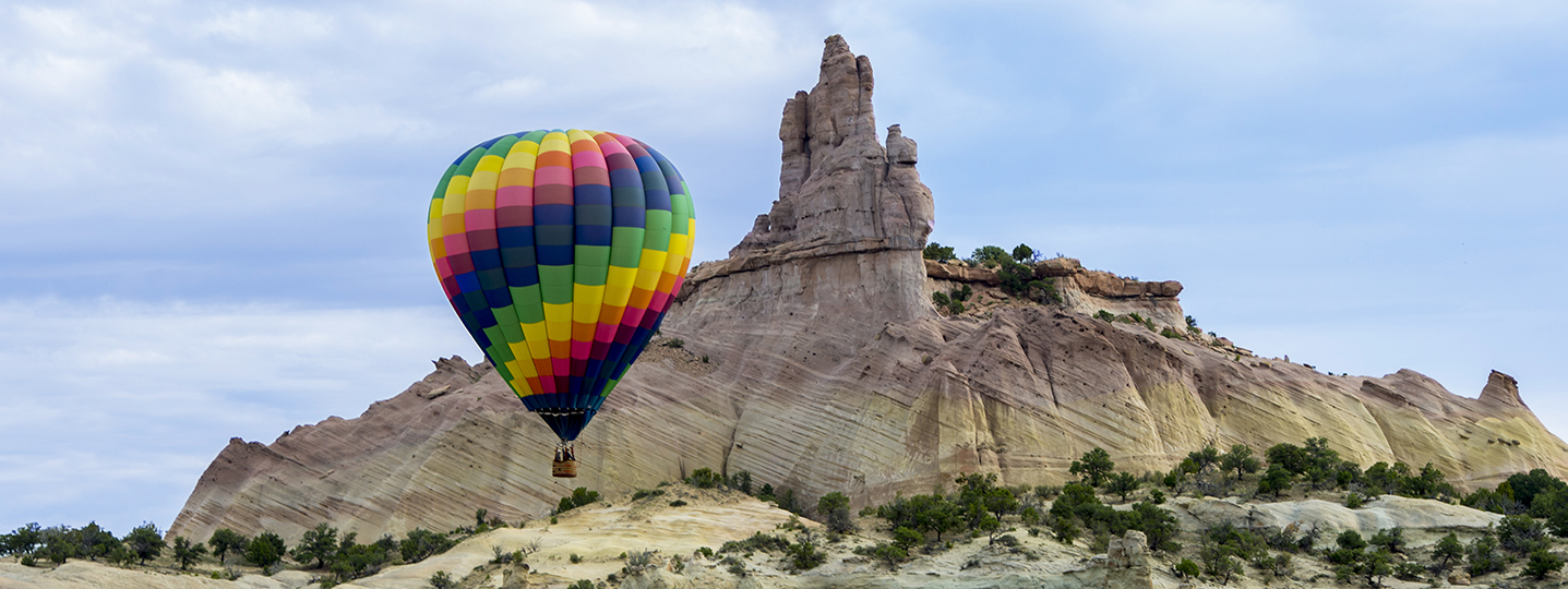 Hot air balloon rising in front of mountain