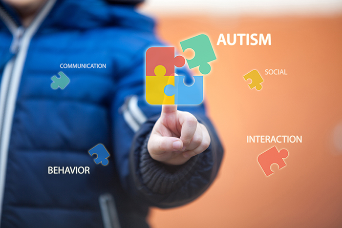Autism Awareness Month graphic featuring a child figure with the autism symbol of puzzle pieces and related words.