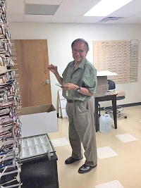 Dennis Yazza sets up the eyeglasses gallery in the new building on moving day.