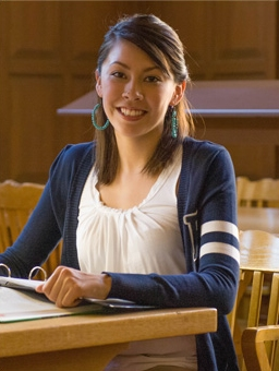 Woman student smiling while sitting in a chair with book in hand.