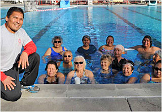 An instructor posing with his water aerobics class.